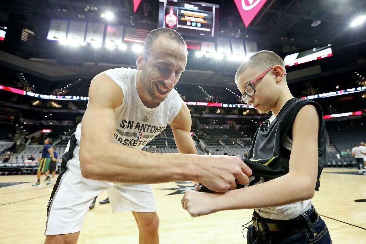 San Antonio Spurs' Manu Ginobili gives an autograph to Ginobili San Miguel-Ramirez, 10, before the Spurs and Utah Jazz game Monday Dec. 14, 2015 at the AT&T Center.