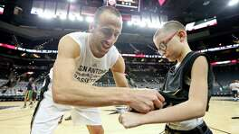 San Antonio Spurs' Manu Ginobili gives an autograph to Ginobili San Miguel-Ramirez, 10, before the Spurs and Utah Jazz game Monday Dec. 14, 2015 at the AT&T Center.