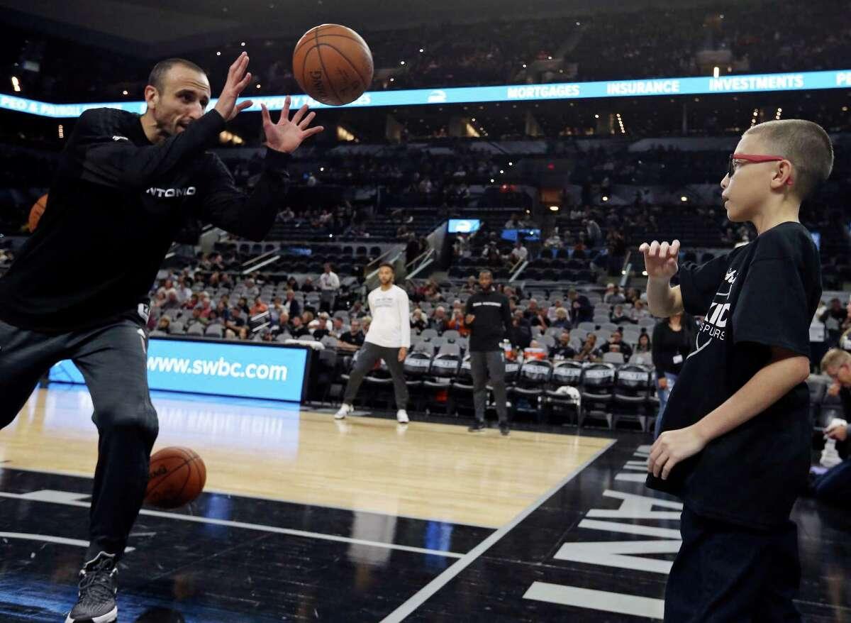 Ginobili San Miguel-Ramirez, 10, throws the ball to San Antonio Spurs' Manu Ginobili during warmups before the game with the Utah Jazz Monday Dec. 14, 2015 at the AT&T Center.