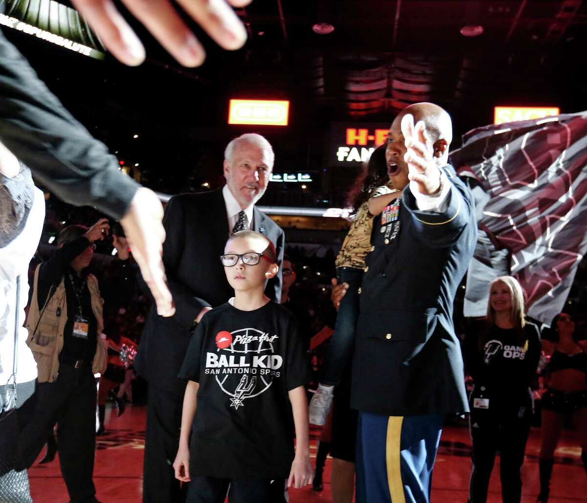 Ginobili San Miguel-Ramirez, 10, (center) and others greet San Antonio Spurs players during introductions as head coach Gregg Popovich (center rear) looks on before the game with the Utah Jazz Monday Dec. 14, 2015 at the AT&T Center.