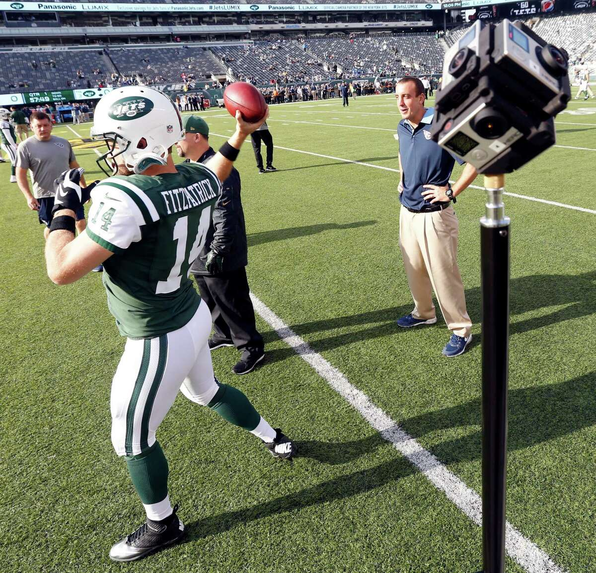 In a Sunday, Dec. 13, 2015, photo, New York Jets quarterback Ryan Fitzpatrick, left, warms up before an NFL football game against the Tennessee Titans as cameras film him at MetLife Stadium in East Rutherford, N.J. (AP Photo/Julio Cortez) ORG XMIT: NJJC211