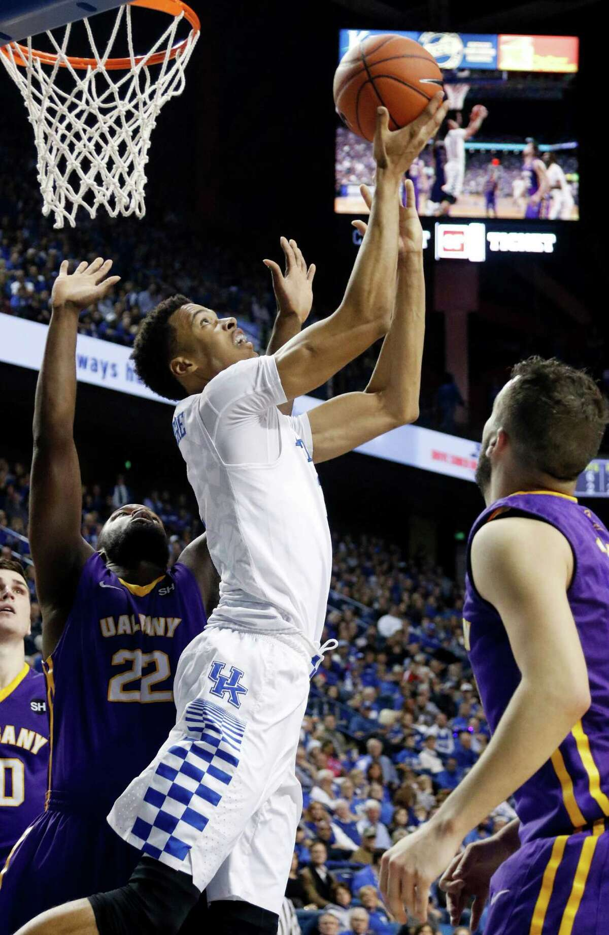 Kentucky's Skal Labissiere, center, shoots between Albany's Richard Peters (22) and Peter Hooley during the second half of an NCAA college basketball game Friday, Nov. 13, 2015, in Lexington, Ky. Kentucky won 78-65. (AP Photo/James Crisp) ORG XMIT: KYJC108