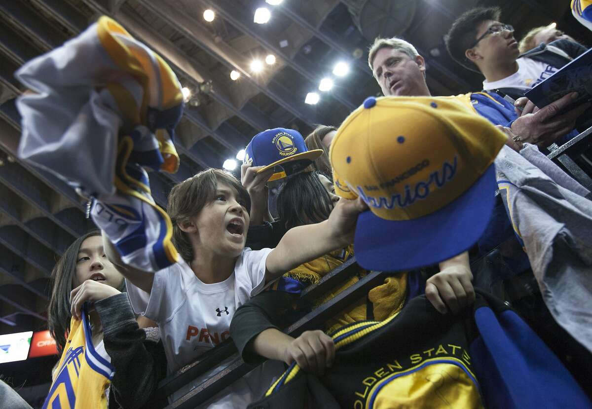 Eight-year-old Christian Riese tries to grab Golden State Warriors guard Stephen Curry's attention before an NBA basketball game against the Milwaukee Bucks, Friday, Dec. 18, 2015, at Oracle Arena in Oakland, Calif.