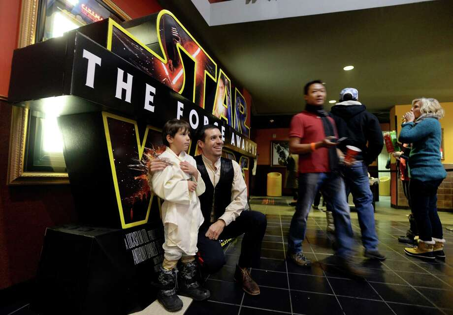 """Chris Geer poses for a photo in front of the Star Wars movie poster with his son Ethan during opening night of """"Star Wars: The Force Awakens"""" at Century Theatre in Boulder, Colo., Thursday, Dec. 17, 2015. (Jeremy Papasso/Daily Camera via AP) NO SALES; MANDATORY CREDIT Photo: Jeremy Papasso, MBO / Daily Camera"""