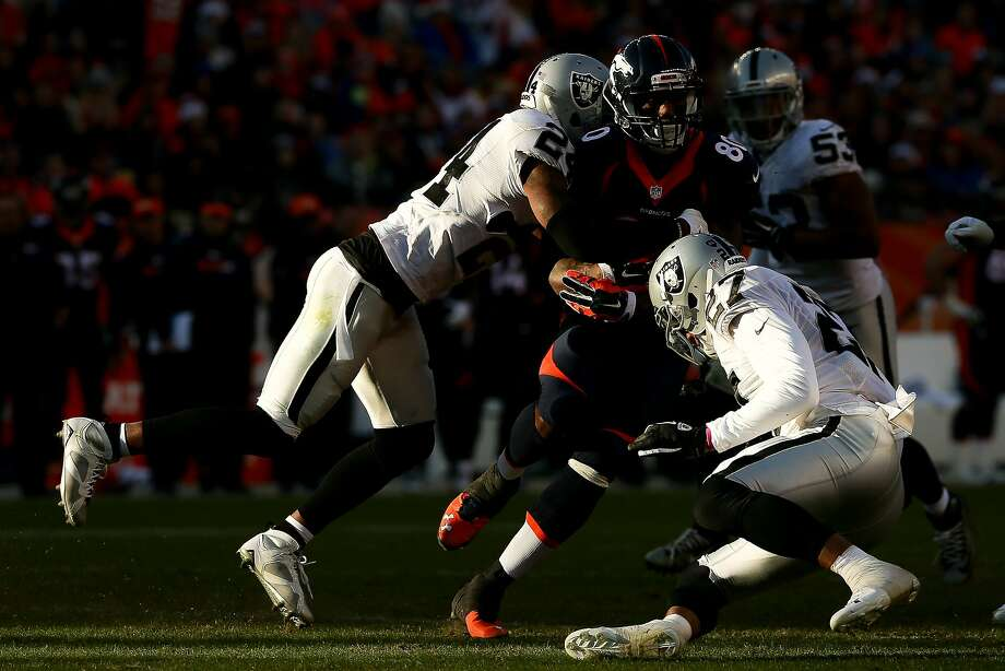 Broncos tight end Vernon Davis is hit by Raiders free safety Charles Woodson (24) and strong safety Taylor Mays (27). Photo: Doug Pensinger, Getty Images