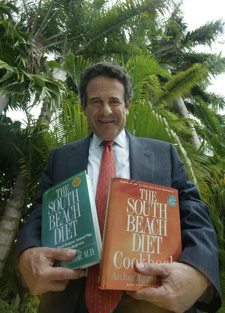 FILE - In this May 6, 2004 file photo,Arthur Agatston, a cardiologist at Mount Sinai Hospital who created the South Beach Diet, poses with two of his books  in his Miami Beach, Fla., home.  The weight-loss company Nutrisystem is buying the South Beach Diet brand for $15 million, reported Friday, Dec. 18, 2015. Agatston will join Nutrisystem's science advisory board after its acquisition from SBD Holdings Group Corp. (AP Photo/Wilfredo Lee) Photo: WILFREDO LEE, STF / AP