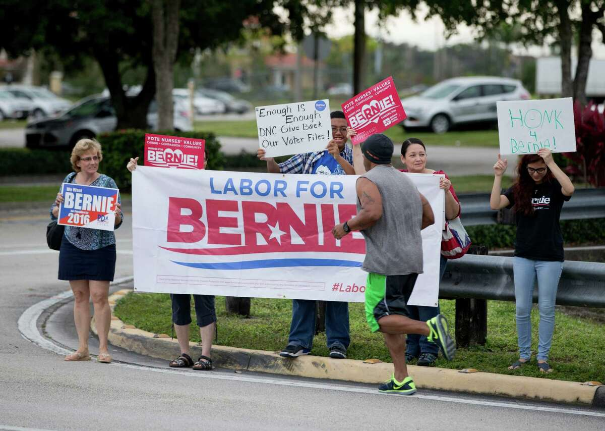A jogger passes a handful of supporters of Bernie Sanders outside Rep. Debbie Wasserman Schultz's district office, Friday, Dec. 18, 2015, in Pembroke Pines, Fla. Sanders' presidential campaign filed a lawsuit against the Democratic Party on Friday after it was temporarily barred from accessing a trove of information about potential voters as punishment for improperly accessing data compiled by the campaign of rival Hillary Clinton. (AP Photo/Wilfredo Lee) ORG XMIT: FLWL117