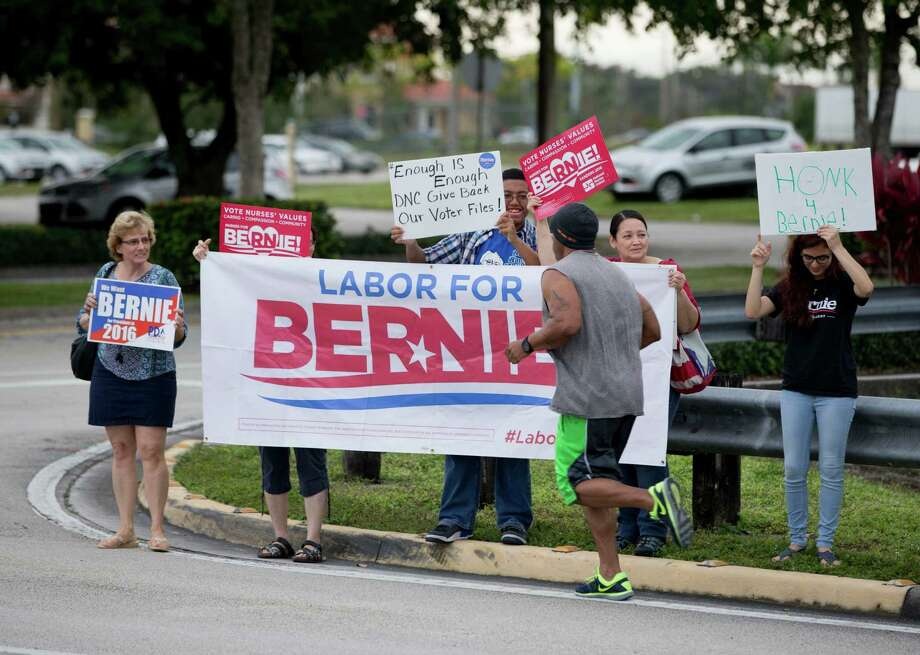 A jogger passes a handful of supporters of Bernie Sanders outside Rep. Debbie Wasserman Schultz's district office, Friday, Dec. 18, 2015, in Pembroke Pines, Fla. Sanders' presidential campaign filed a lawsuit against the Democratic Party on Friday after it was temporarily barred from accessing a trove of information about potential voters as punishment for improperly accessing data compiled by the campaign of rival Hillary Clinton. (AP Photo/Wilfredo Lee) ORG XMIT: FLWL117 Photo: Wilfredo Lee / AP