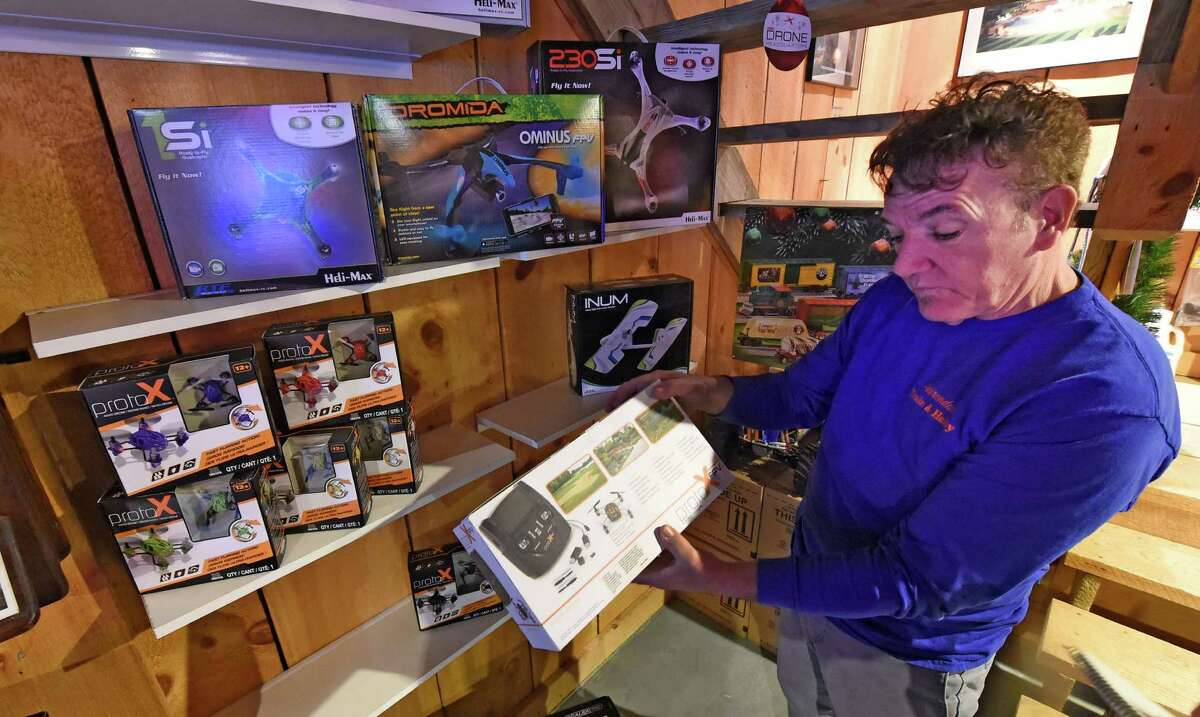 Manager Jim Grotto stands in front of a display of unmanned flying machines on display at the Adirondack Train & Hobby lines the wall Thursday Dec. 17, 2015 in Saratoga Springs, N.Y. (Skip Dickstein/Times Union)