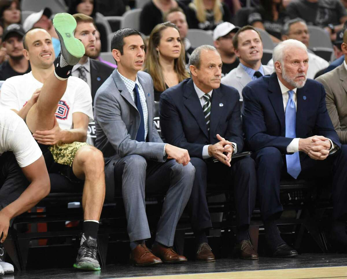 Manu Ginobili of the Spurs (left) stretches as he sits on the bench next to assistant coaches James Borrego, Ettore Messina and head coach Gregg Popovich during the game against the Charlotte Hornets at the AT&T Center on Nov. 7. 2015.