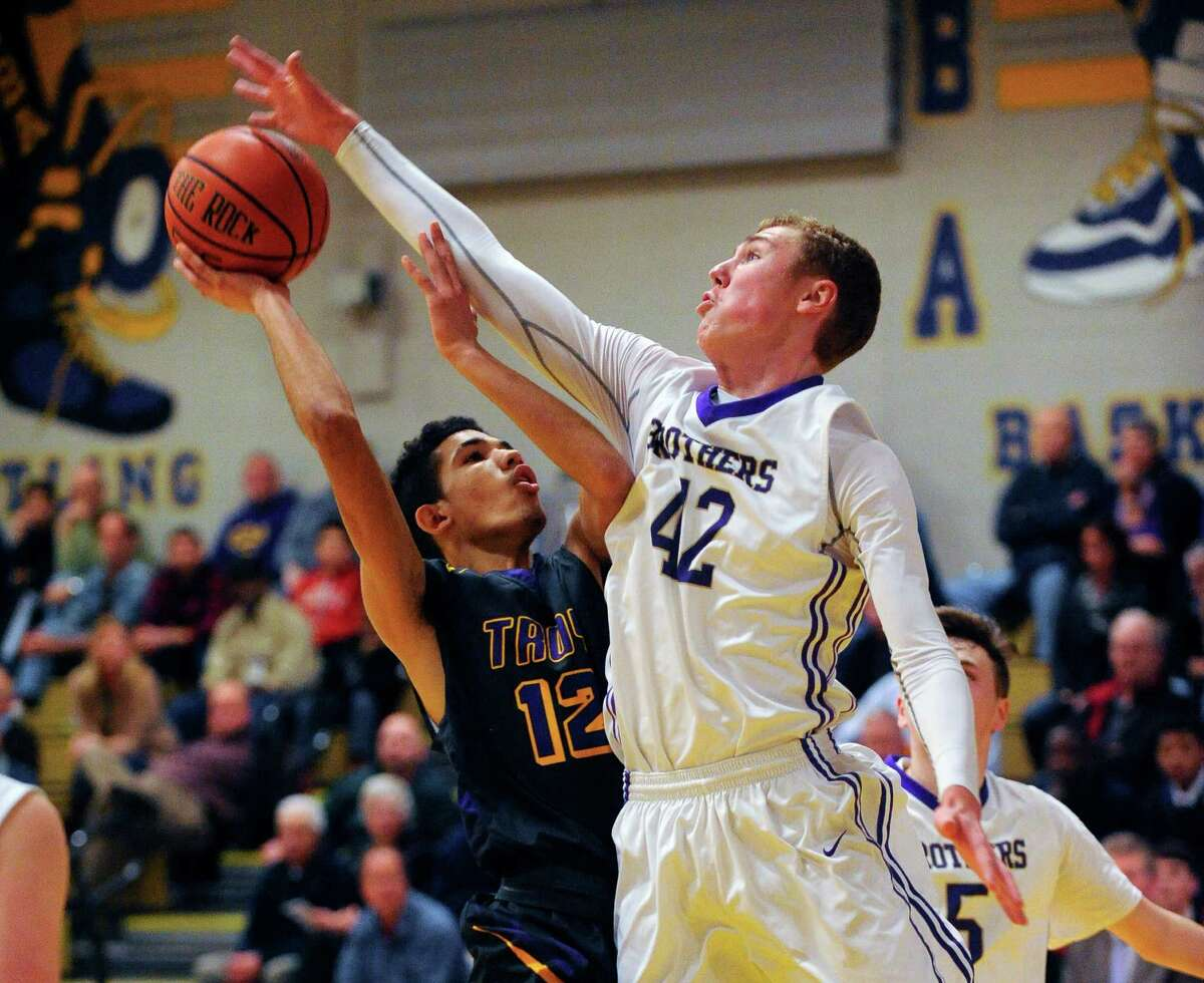 Troy's Daniel Buie (12) is fouled by Christian Brothers Academy's Scott Trobridge (42) during the first half of their boys' high school basketball game on Thursday, Dec. 18, 2015, in Colonie, N.Y. (Hans Pennink / Special to the Times Union) ORG XMIT: HP102