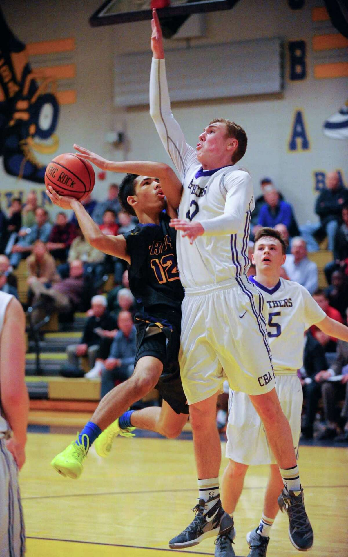 Troy's Daniel Buie (12) is fouled by Christian Brothers Academy's Scott Trobridge (42) during the first half of their boys' high school basketball game on Thursday, Dec. 18, 2015, in Colonie, N.Y. (Hans Pennink / Special to the Times Union) ORG XMIT: HP103