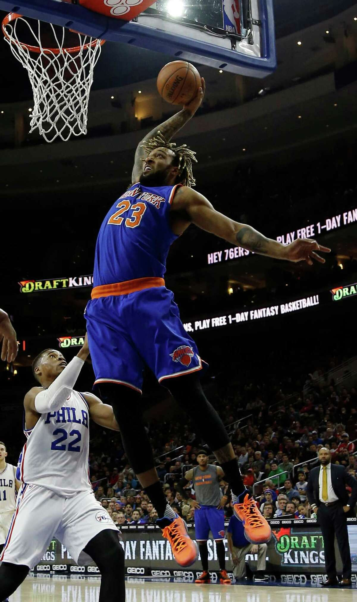 New York Knicks' Derrick Williams, right, goes up for a dunk against Philadelphia 76ers' Richaun Holmes during the first half of an NBA basketball game, Friday, Dec. 18, 2015, in Philadelphia. (AP Photo/Matt Slocum) ORG XMIT: PXC105