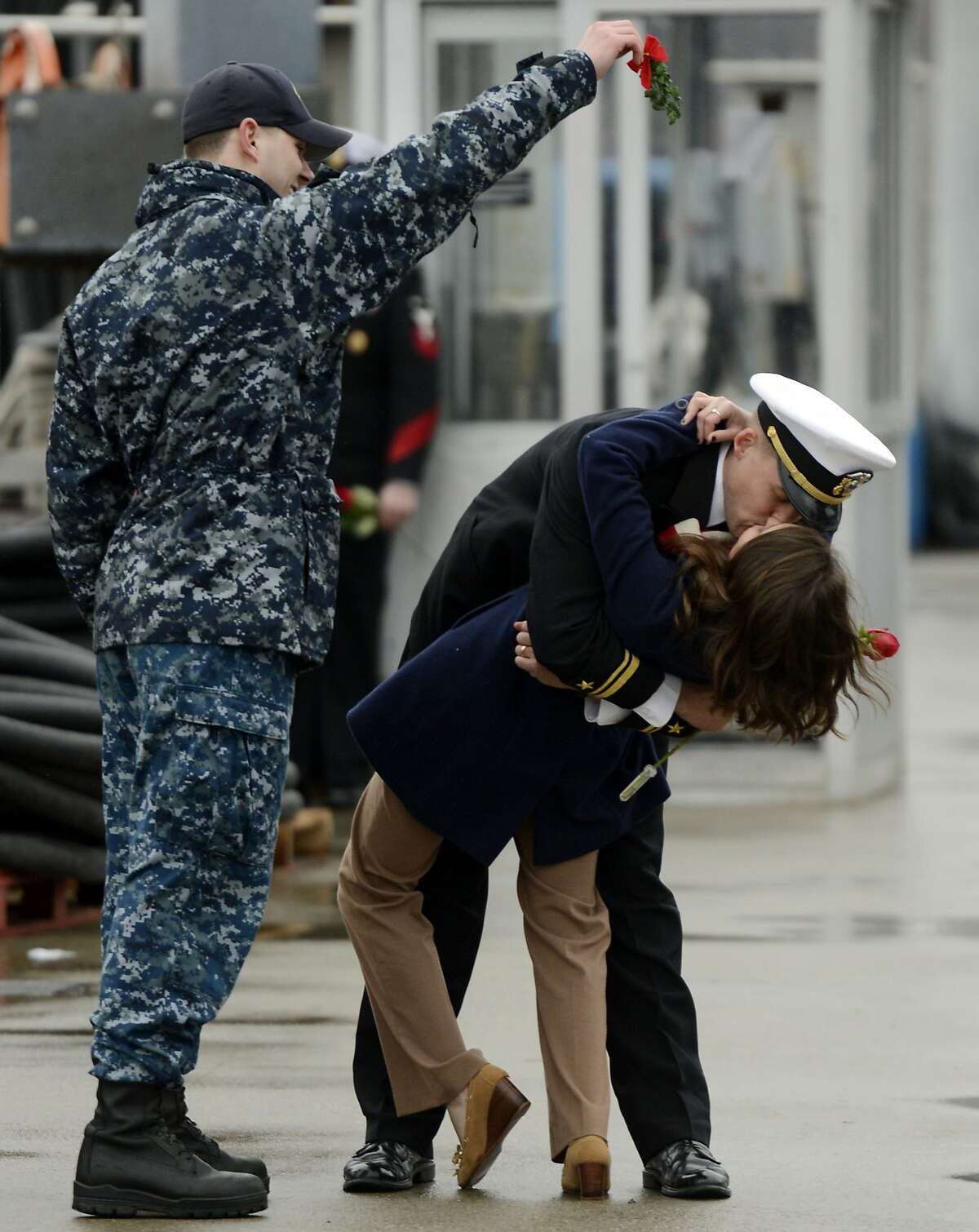 U.S. Navy Lt. jg. Stephen Bogdanowicz, left, holds a sprig of mistletoe as Ensign Morgan Oblinsky and his wife Katie enjoy the ceremonial first kiss as the navy attack submarine USS Hartford returns to the U.S. Navy Submarine Base in Groton, Conn., Friday, Dec. 18, 2015, following a six-month deployment to the European Command Areas of Responsibility. Hartford, with a crew of around 130 officers and enlisted personnel, made port calls in Faslane, Scotland and Rota, Spain during the deployment. (Sean D. Elliot/The Day via AP)