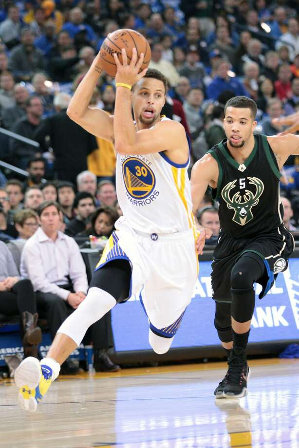 Golden State Warriors guard Stephen Curry (30) dribbles past Milwaukee Bucks guard Michael Carter-Williams (5) during the first half of an NBA basketball game, Friday, Dec. 18, 2015, at Oracle Arena in Oakland, Calif. Photo: Santiago Mejia, Special To The Chronicle