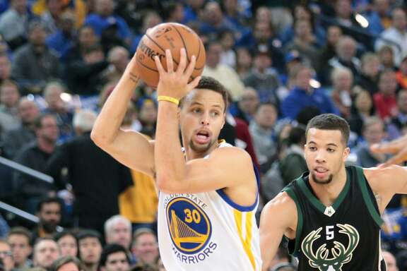 Golden State Warriors guard Stephen Curry (30) dribbles past Milwaukee Bucks guard Michael Carter-Williams (5) during the first half of an NBA basketball game, Friday, Dec. 18, 2015, at Oracle Arena in Oakland, Calif.