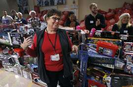 Laurrie Ferreira organizes the army of volunteers that will escort children through the mountain of toys at the annual holiday toy giveaway at Glide Memorial Church in San Francisco, Calif. on Saturday, Dec. 19, 2015.