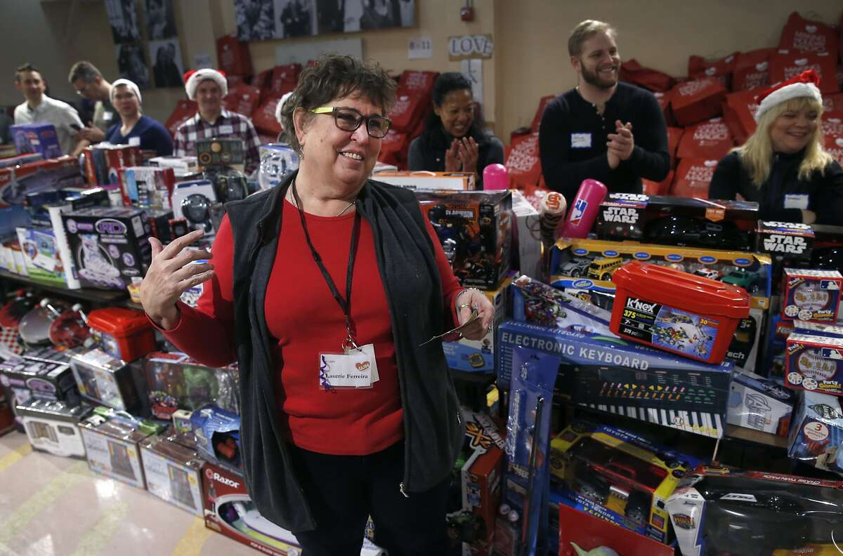 Laurrie Ferreira leads volunteers who escort children through the toys at the annual toy giveaway at Glide Memorial Church in San Francisco on Saturday, Dec. 19, 2015.