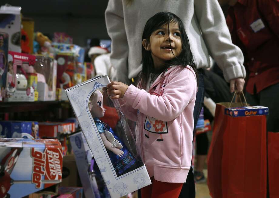 Jennifer Jimenez, 5, selects a doll as a Christmas present at the annual holiday toy giveaway at Glide Memorial Church in San Francisco, Calif. on Saturday, Dec. 19, 2015. Photo: Paul Chinn, The Chronicle