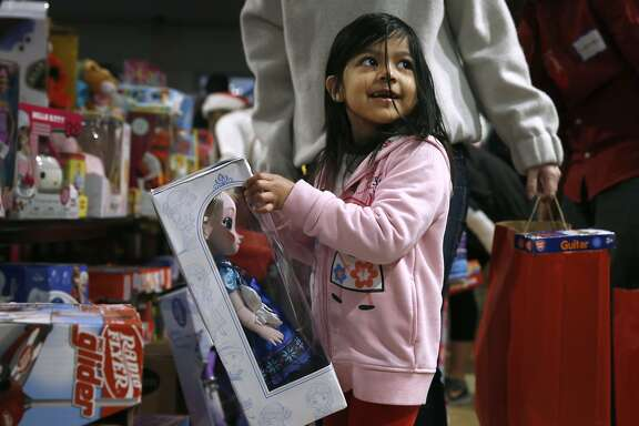Jennifer Jimenez, 5, selects a doll as a Christmas present at the annual holiday toy giveaway at Glide Memorial Church in San Francisco, Calif. on Saturday, Dec. 19, 2015.
