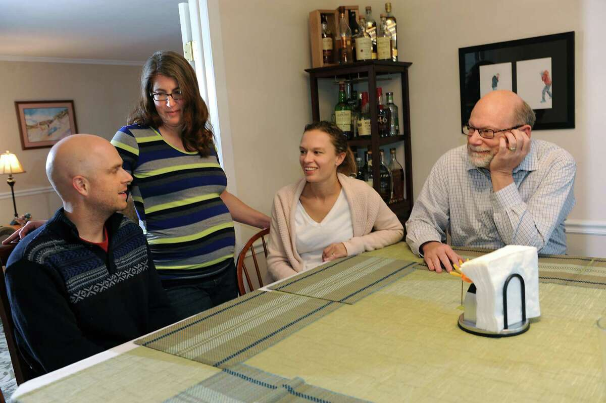 Ryan Levering, left, talks with his stepmother Abby, second from left, his wife Terrill and his father Bill at Bill and Abby's home on Friday, Nov. 27, 2015 in Niskayuna, N.Y. Abby is the gestational surrogate for her stepson and his wife. She is due in February. (Lori Van Buren / Times Union)