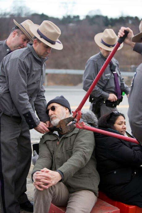 Police use bolt cutters to remove a locking device around James Cromwell's neck during a protest at a power plant under construction in Wawayanda, N.Y. Photo: Erik Gliedman /Times Herald-Record / Times Herald-Record