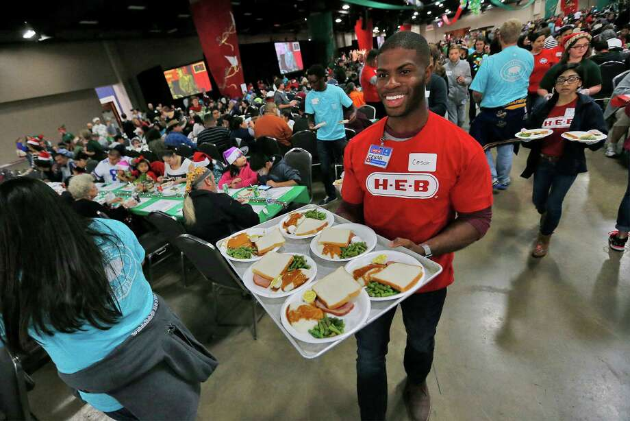 H-E-B employee Cesar Carter carries a plate of food for guests arriving at the 2015 H-E-B Feast of Sharing at the Convention Center on Saturday, Dec. 19, 2015. Thousands of people annually gather for the pre-Christmas event to share a meal and to take in the festivities hosted by the local grocery chain. This year marks the 23rd year that H-E-B has hosted the event. The company has since expanded the feast to 22 other cities in Texas. (Kin Man Hui/San Antonio Express-News) Photo: Kin Man Hui, Staff / San Antonio Express-News / ©2015 San Antonio Express-News