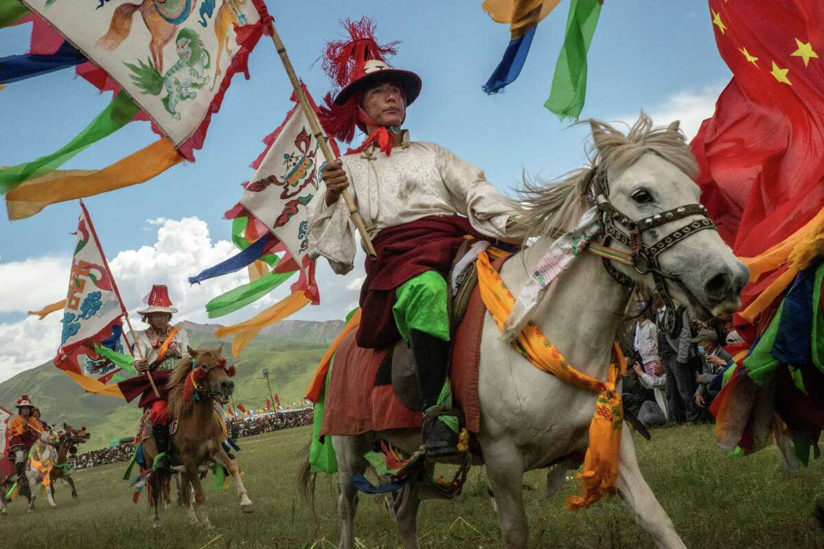 Tibetan horsemen display their skills at a govern- ment-organized festival in Yushu, China, in July.