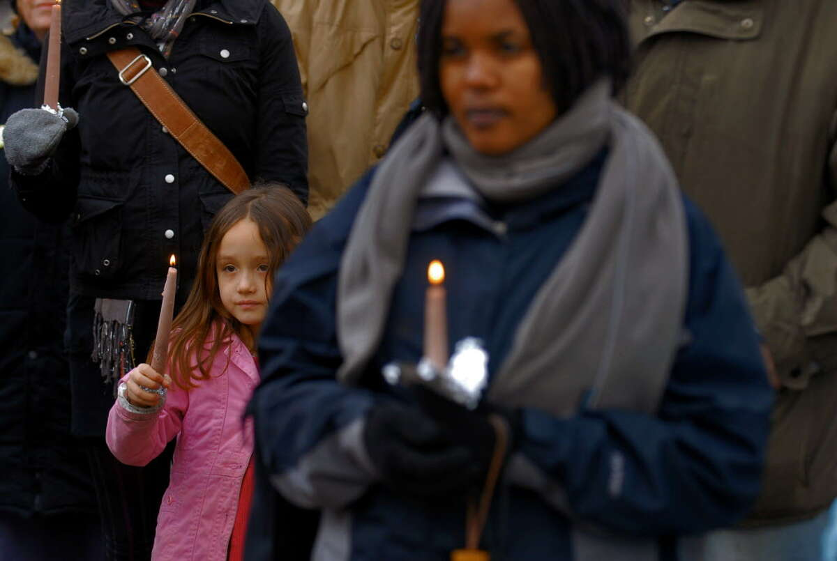 Maura Palden of Albany, left, whose father is from Tibet, and Marina Byamukama of Uganda, right, were some of over 50 people who came to a vigil to remember victims of the shootings at the American Civic Association in Binghamton last week, in Albany, NY Wednesday evening April 8, 2009. Marina is an intern with the NYS Senate. Her roommate's mother was killed in the attack last week. (roommate's name is Christia Zobniw, and her late mother's name is Maria Zobniw)(Philip Kamrass / Times Union)