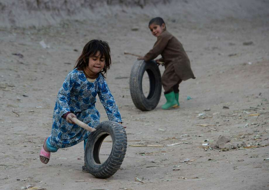 In this photograph taken on December 18, 2015, Afghan children play with tyrss in a village on the outskirts of Jalalabad in Nangarhar province. Photo: Noorullah Shirzada, AFP / Getty Images