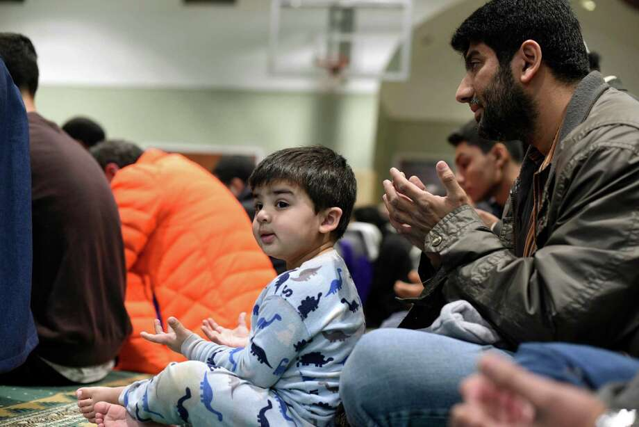Salim Modak (right) and his son, Affan, pray at the All Dulles Area Muslim Society  Center in Sterling, Va., on Friday. Worship centers across the U.S. are beefing up security in the wake of attacks this year. Photo: Sait Serkan Gurbuz /Associated Press / FR171401 AP