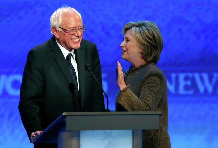 Hillary Clinton, right, speaks to Bernie Sanders during a break at the Democratic presidential primary debate Saturday, Dec. 19, 2015, at Saint Anselm College in Manchester, N.H. (AP Photo/Jim Cole) Photo: Jim Cole, STF / Associated Press / AP