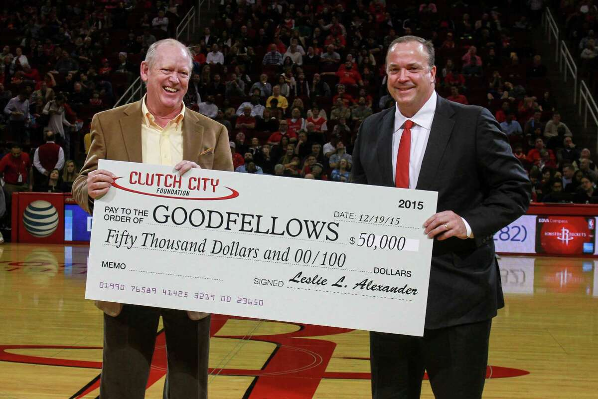 Houston Rockets CEO Tad Brown, right, presents a $50,000 check to Houston Chronicle Chairman Jack Sweeney for the Goodfellows program during Saturday's game.