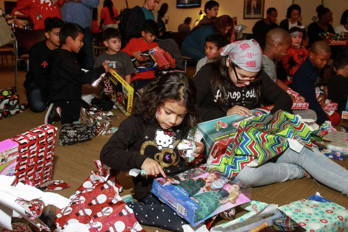 Goodfellows recipients open presents during a party at the Rockets game Saturday. The nonprofit provides toys to needy children for Christmas.