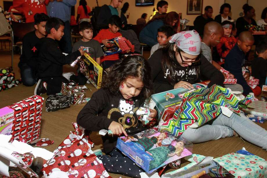 Goodfellows recipients open presents during a party at the Rockets game Saturday. The nonprofit provides toys to needy children for Christmas. Photo: Gary Fountain, For The Chronicle / Copyright 2015 Gary Fountain