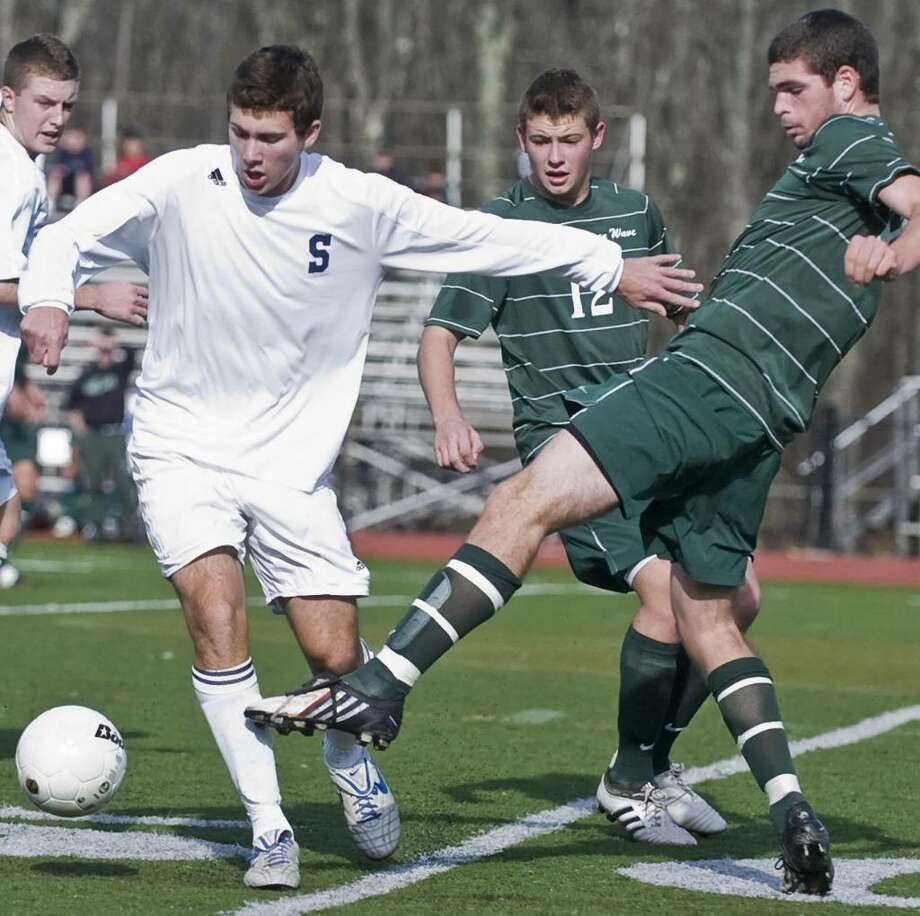Staples senior Alan Reiter pushes off New Milford senior Zane Swanson during a boys soccer game at Ridgefield. Saurday, Nov. 21, 2009 Photo: Scott Mullin, ST