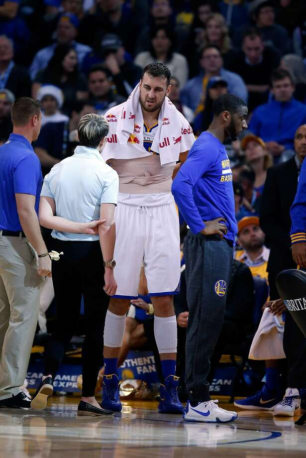 Andrew Bogut talks with a trainer during the Warriors' victory Friday, when he played just 5 minutes and 20 seconds. Photo: Ezra Shaw, Getty Images