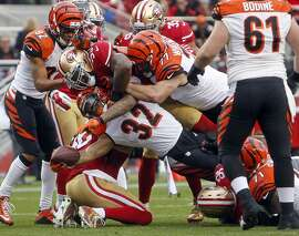 Cincinnati Bengals' Jeremy Hill reaches for the goal line while being tackled by San Francisco 49ers' NaVorro Bowman in 2nd quarter during NFL game in Santa Clara, Calif., on Sunday, December 20, 2015.
