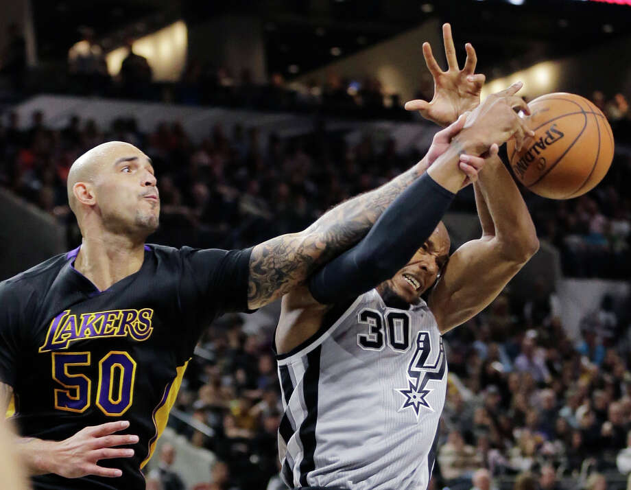 Los Angeles Lakers center Robert Sacre (50) and San Antonio Spurs forward David West (30) battle for a rebound during the first half of an NBA basketball game, Friday, Dec. 11, 2015, in San Antonio. (AP Photo/Eric Gay) Photo: Eric Gay, STF / Associated Press / AP