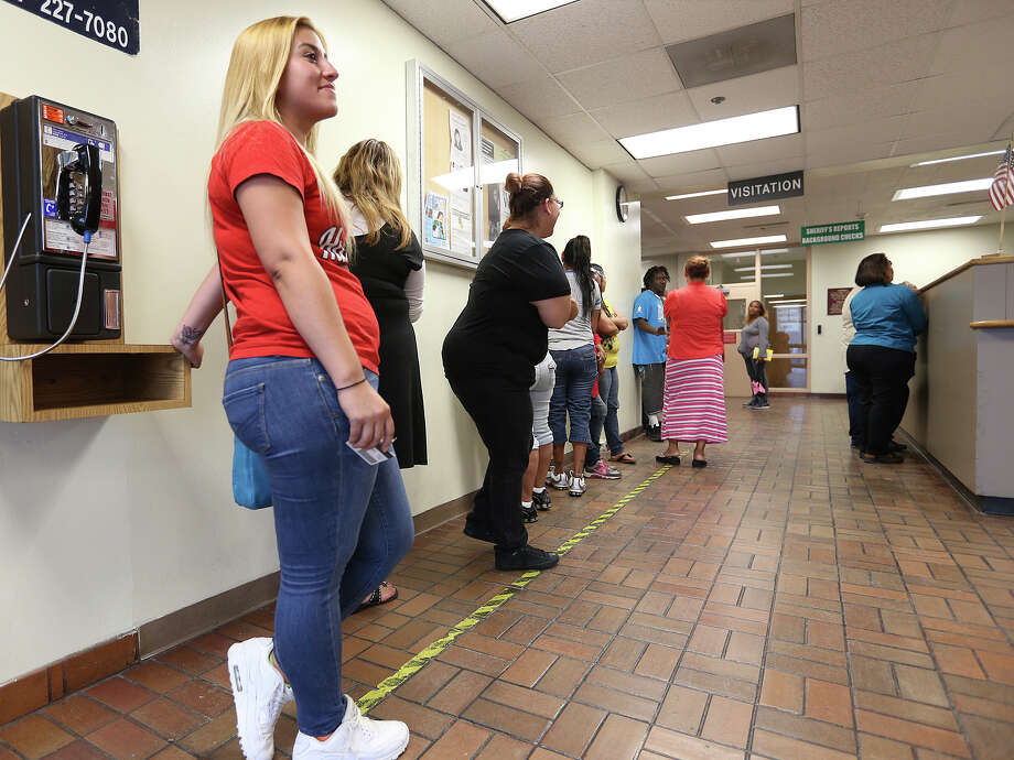 This file photo shows family members and others in line to visit inmates at the Bexar County Jail last June. The Bexar County Sheriff's Department is moving toward video visitations next year. Photo: Jerry Lara /For The San Antonio Express-News / ©2015 San Antonio Express-News