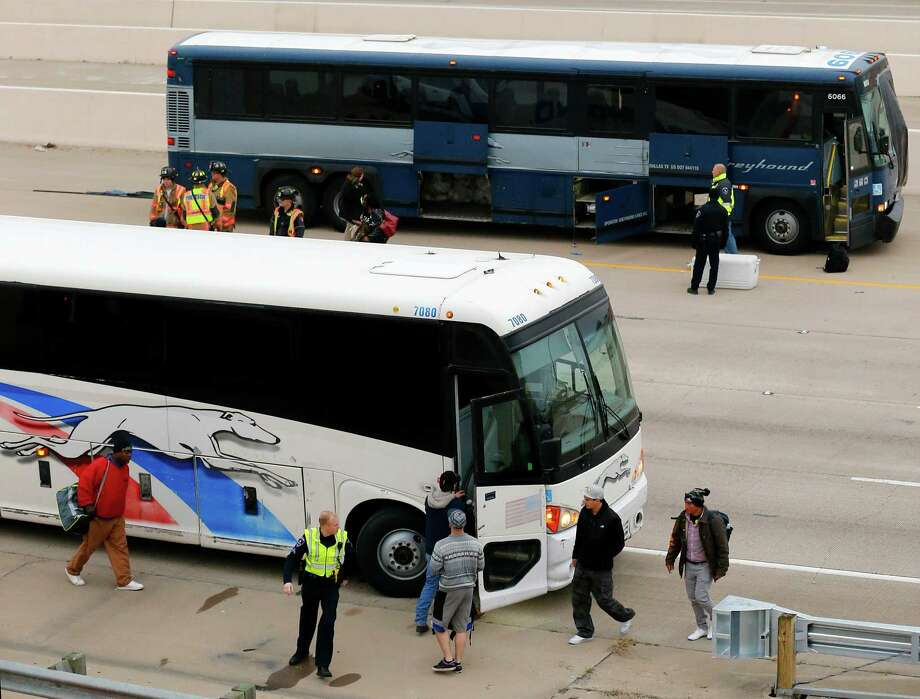 Passengers board another Greyhound bus after the one they were on struck a stalled SUV in the fast lane on westbound Interstate 30 near Collins Street in Arlington. A woman in the SUV was killed and a man in the SUV was seriously injured. More than a dozen people on the bus were injured, too. Photo: Tom Fox /Associated Press / The Dallas Morning News