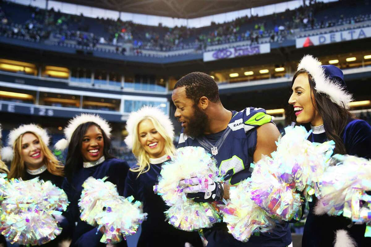 Seahawks' Michael Bennett jokes around with the SeaGals after the Seahawks game against Cleveland, Sunday, Dec. 20, 2015 at CenturyLink Field. The Seahawks won 30-13.