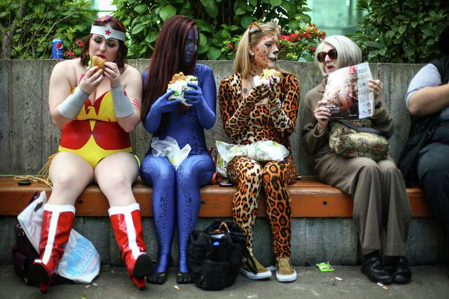 From left, Stephanie Galver as Wonder Woman, Amber Hague as Mystique, and  Anna Harris as a cheetah eat lunch during day one of Emerald City Comicon at the Washington State Convention Center on Friday, March 27, 2015. The three day convention is the largest comic book and pop culture convention in the Pacific Northwest. The convention features cosplay, comic books, celebrities and more. Photo: JOSHUA TRUJILLO, SEATTLEPI.COM / SEATTLEPI.COM
