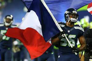 Seattle's Cliff Avril carries the flag of France onto the field in support of victims of Friday's terrorist attacks, before the Seahawks game against the Cardinals, Sunday, Nov. 15, 2015 at CenturyLink Field.