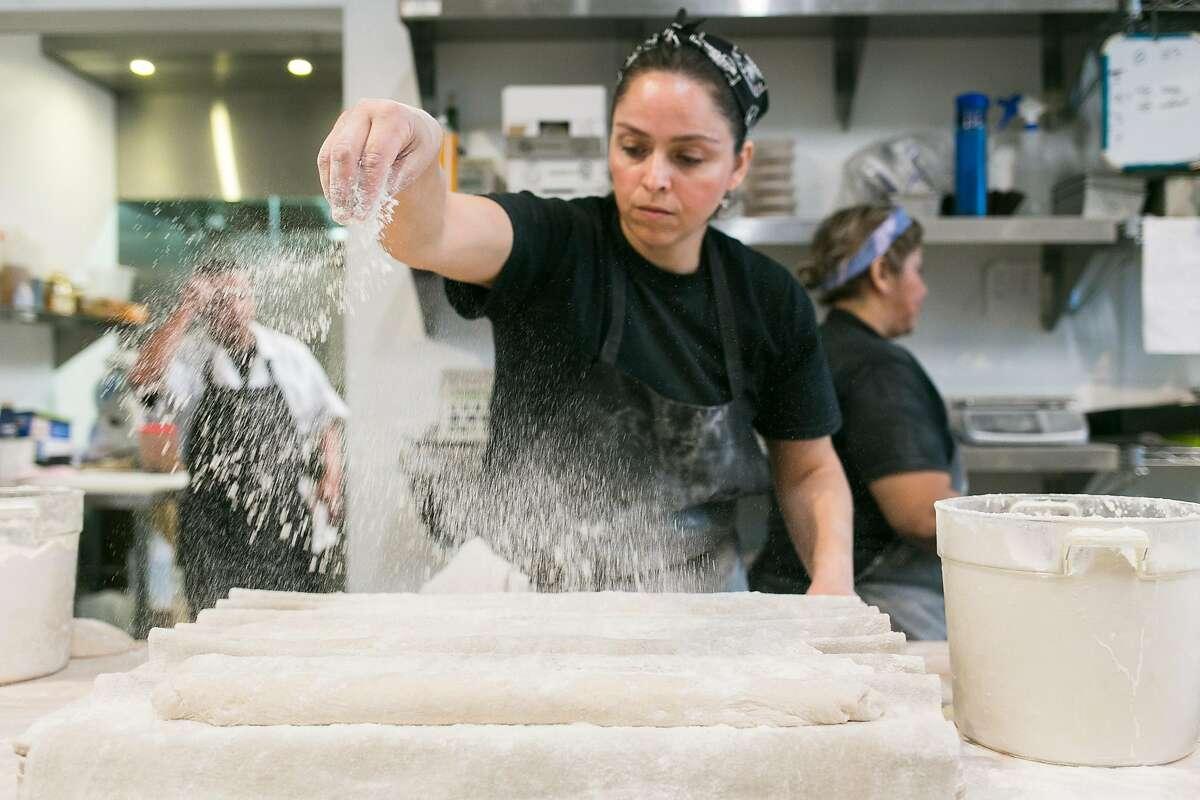 Gabriella Cisneros dusts flour on fresh dough at Firebrand Artisan Breads.