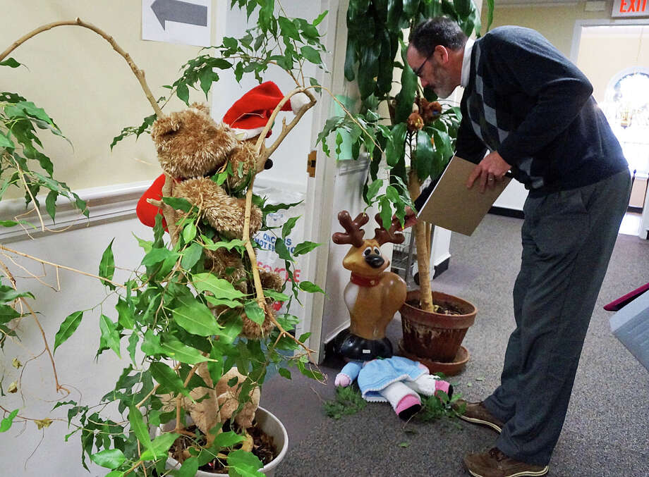 Asst. Planning Director Jim Wendt checks out the Finance Department's entry into a door decorating contest, in which grandma got run over by a reindeer. Photo: Genevieve Reilly / Hearst Connecticut Media / Fairfield Citizen
