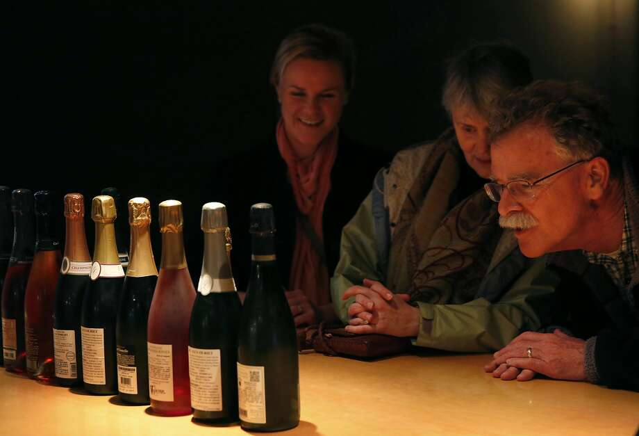 Jeff Innes (right) and his family, Sue Hammond (center) and Lindsey Innes, study their Champagne selections at the San Francisco Champagne Society. Photo: Leah Millis, San Francisco Chronicle