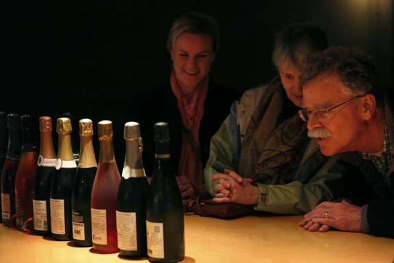 Family members, from left, Lindsey Innes, 30, Sue Hammond, 62, and Jeff Innes, 62, look over the champagne selection as Bill Marci places bottles in front of them for pouring at the San Francisco Champagne Society in Marci's apartment Dec. 19, 2015 in San Francisco, Calif.