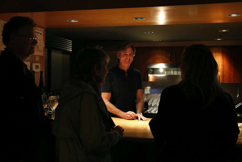 Bill Marci chats with his first reservation of the evening at his San Francisco Champagne Society, which he hosts in his home. Photo: Leah Millis, San Francisco Chronicle