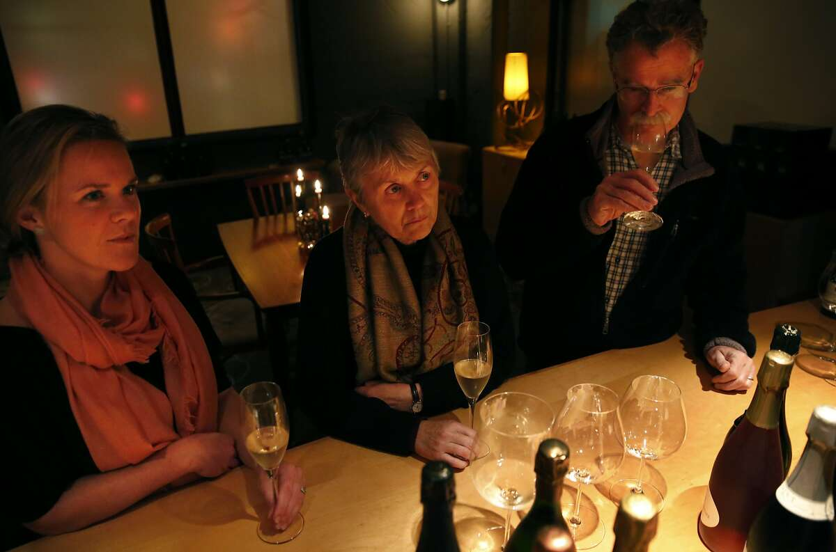 Family members, from left, Lindsey Innes, 30, Sue Hammond, 62, and Jeff Innes, 62, listen to Bill Marci as he discusses different types of champagne glasses during a pouring at the San Francisco Champagne Society in Marci's apartment Dec. 19, 2015 in San Francisco, Calif.